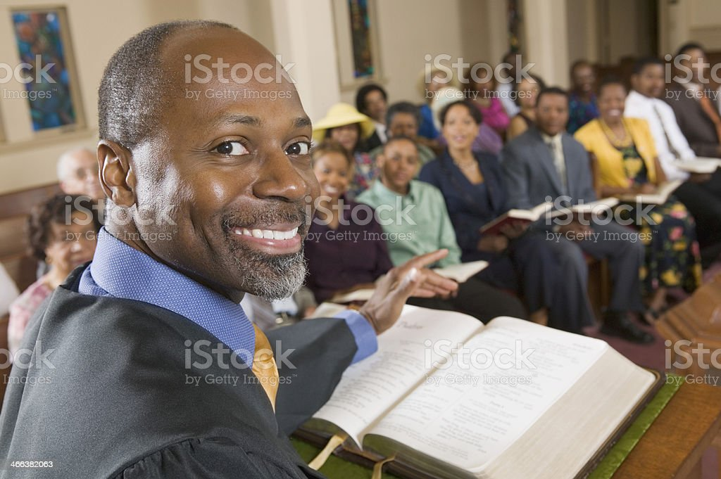 Smiling preacher at the pulpit in front of his congregation  stock photo