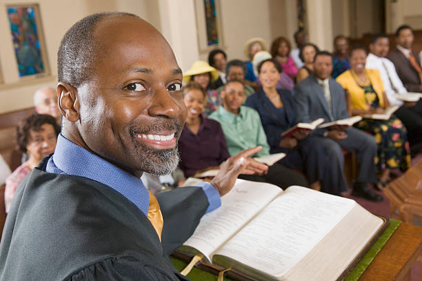 smiling preacher at the pulpit in front of his congregation  - preacher stock photos and pictures