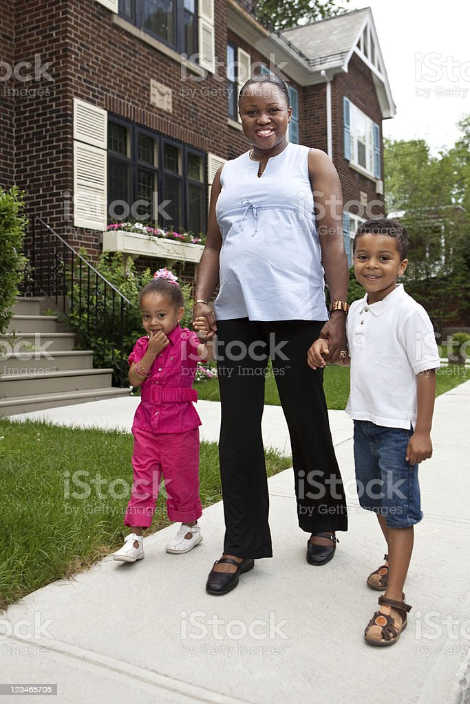 Smiling pregnant black mother holding children's hands royalty-free stock photo