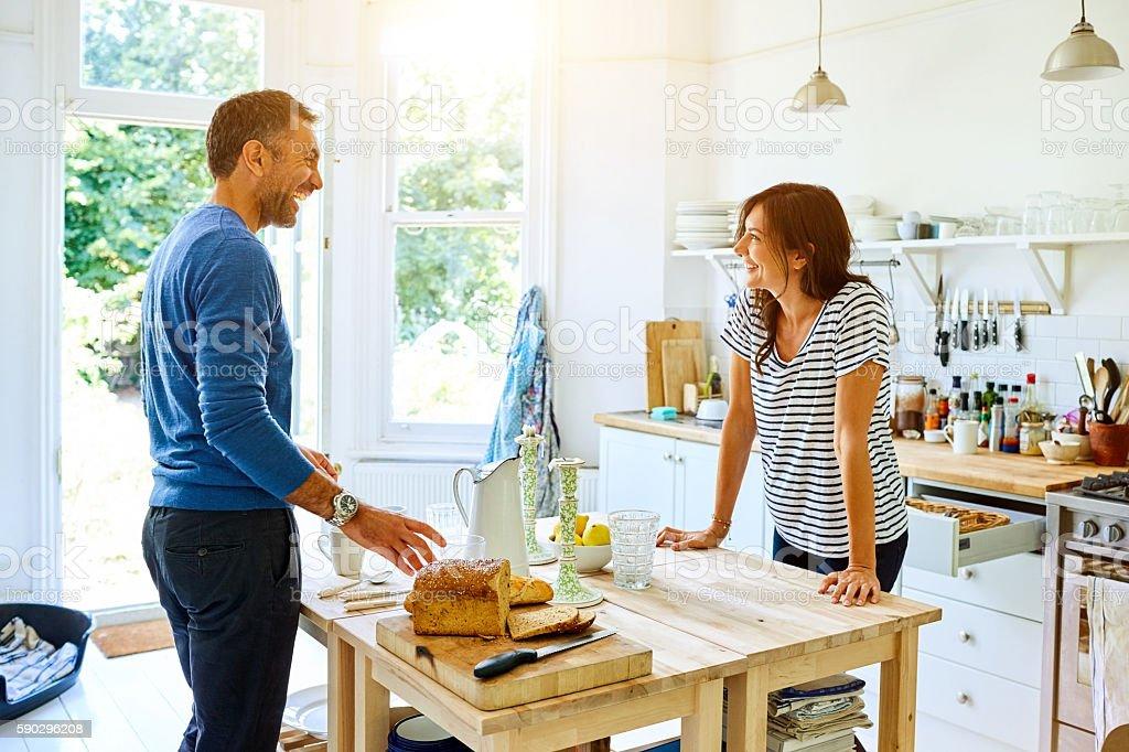 Smiling pregnant couple preparing breakfast in kitchen royaltyfri bildbanksbilder