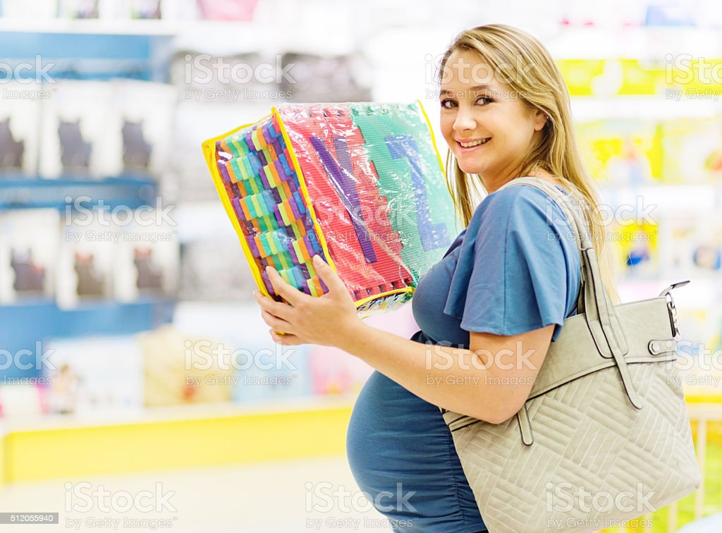 Smiling pregnant woman choosing alphabet soft-foam floor tiles stock photo
