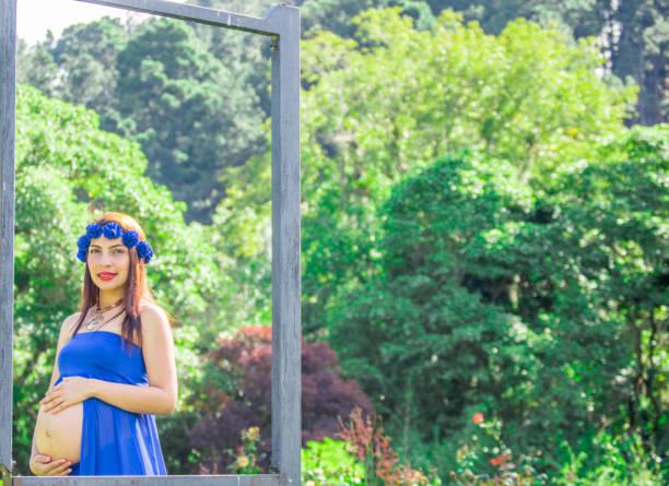 lächelnde schwangere frau in einem park mit blauen drees, gestell eisen - drees und sommer stock-fotos und bilder