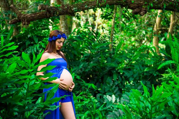 schwangere frau in einem park mit blauen drees, lächelnd, in den wald - drees und sommer stock-fotos und bilder