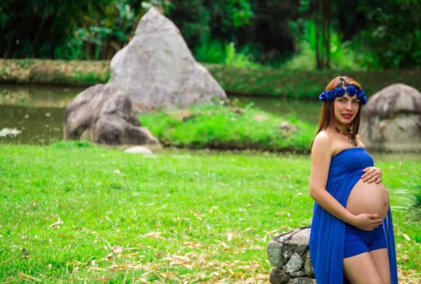 lächelnde schwangere frau in einem park mit blauen drees, in der nähe des sees - drees und sommer stock-fotos und bilder