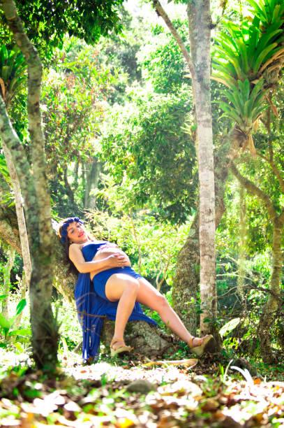 lächelnde schwangere frau in einem park mit blauen drees, schlafen auf das licht der sonne - drees und sommer stock-fotos und bilder