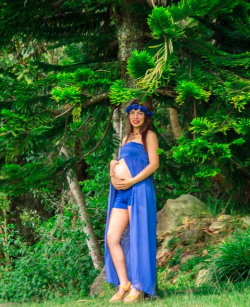 schwangere frau in einem park mit blauen drees, unter dem großen baum lächelnd - drees und sommer stock-fotos und bilder