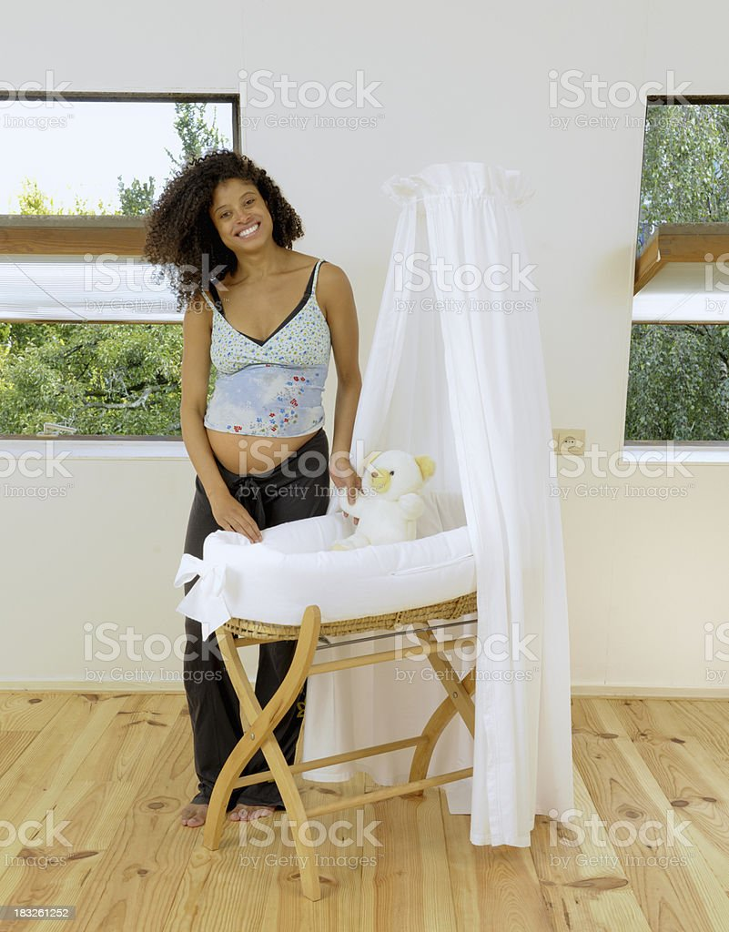 full length shot of a smiling pregnant woman standing behind empty...