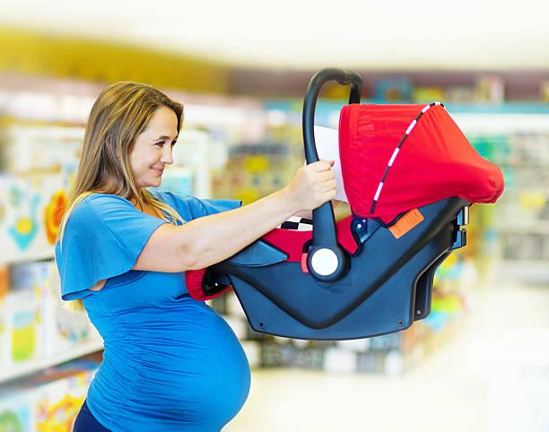lächelnd schwangere frau, die ein kindersitz - mutterschutzfrist stock-fotos und bilder