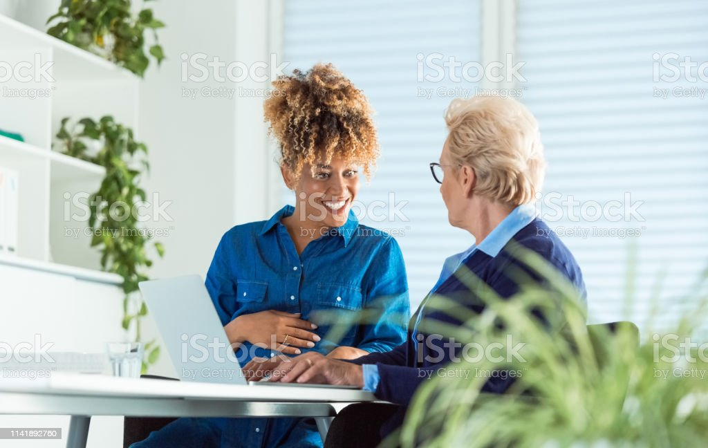 Smiling pregnant woman looking at senior colleague Smiling pregnant businesswoman looking at elderly colleague. Business professionals are planning projects in office. Senior woman is using laptop. 35-39 Years Stock Photo
