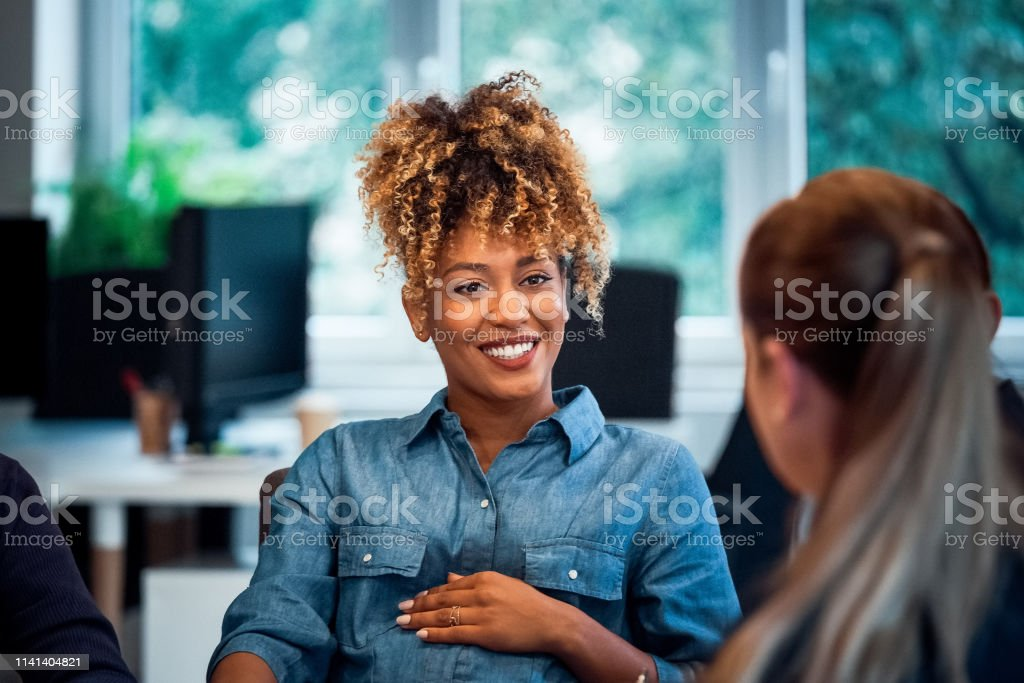 Smiling pregnant woman working in new office Confident smiling businesswoman looking at colleague. Pregnant expertise is working in new office. Business professionals are discussing. 35-39 Years Stock Photo
