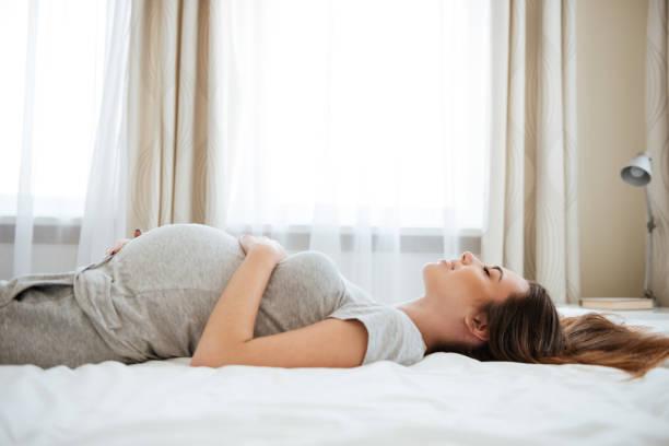 gülümseyen hamile genç kadın yatakta yatan ve dinlenen - yatmak stok fotoğraflar ve resimler
