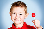 A cute, freckled pre-school boy grins mischievously as he holds up a red lollipop sweet. Delicious!