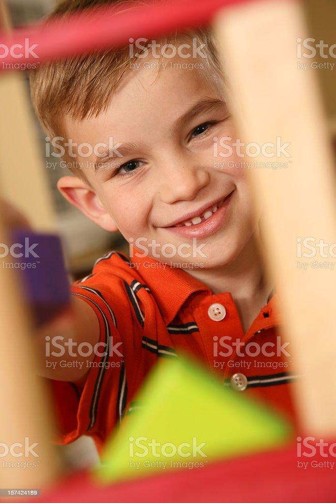 Smiling preschool boy looking through built blocks royalty-free stock photo