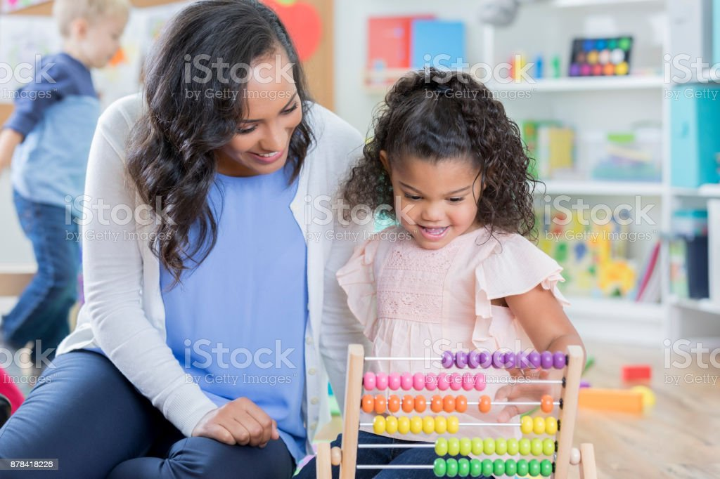 Caring African American female preschool teacher helps mixed race...