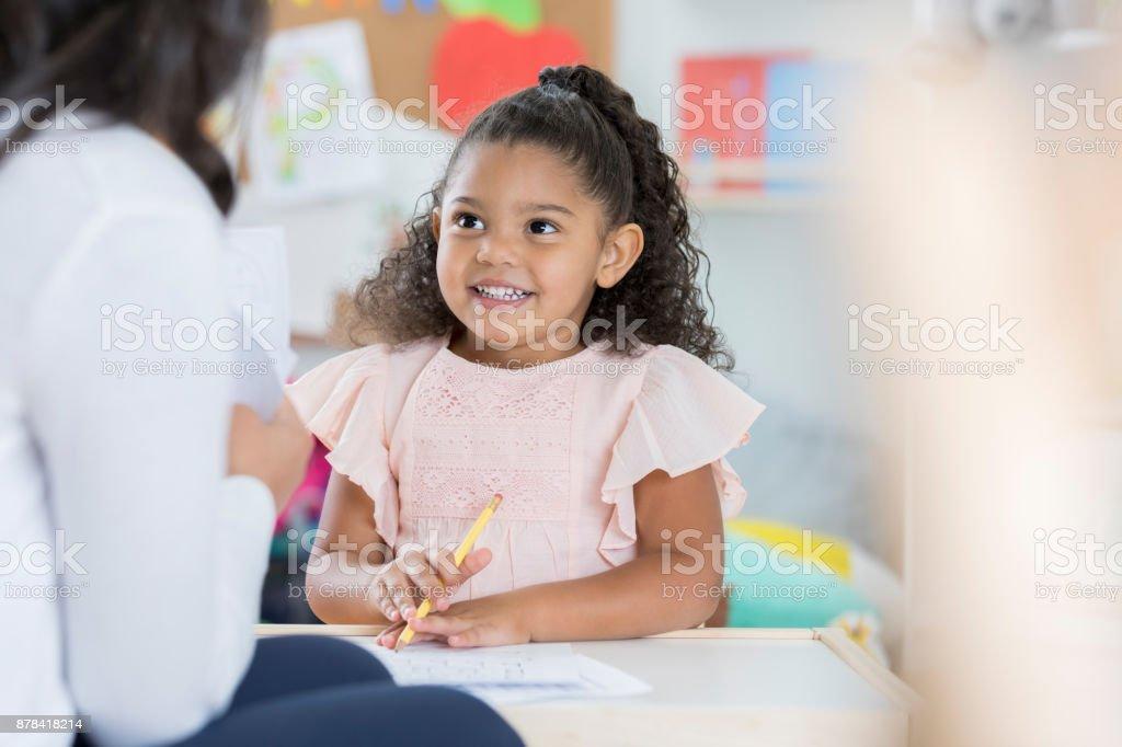 Smiling preschooler talks with teacher stock photo