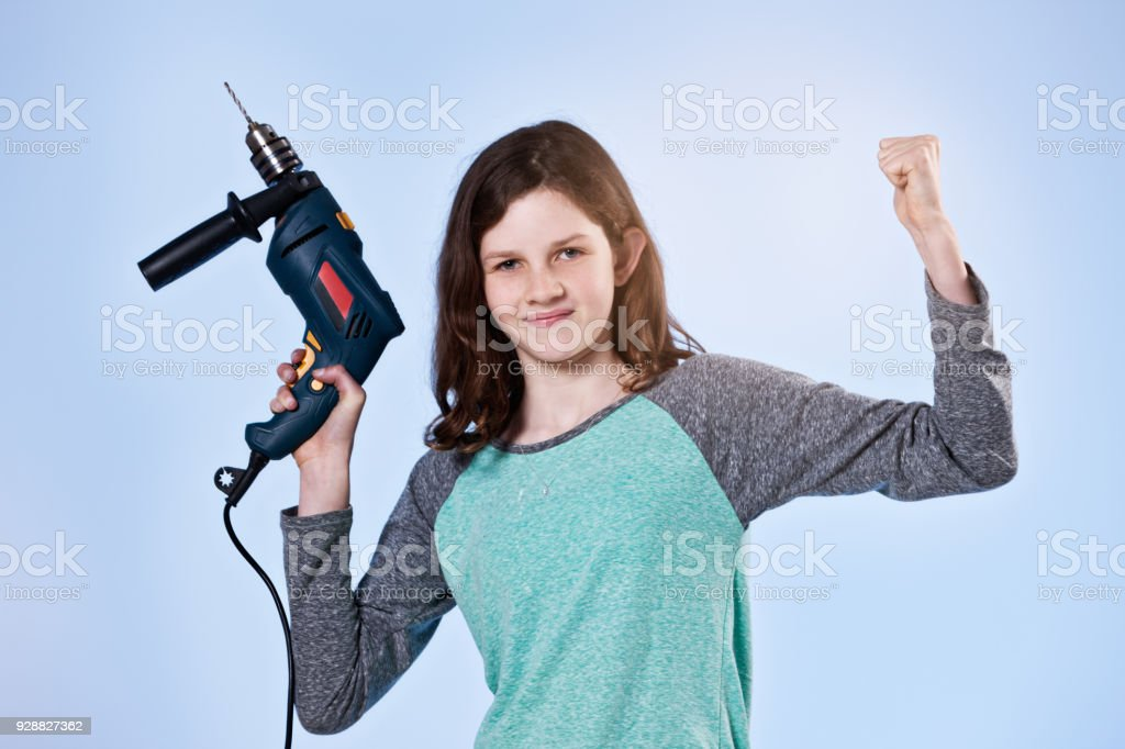 Smiling pre-teen girl holding electric drill has girl power stock photo