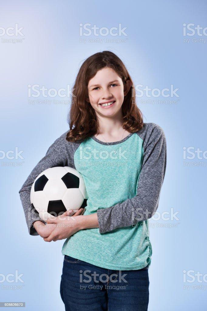 Smiling pre-teen girl holding soccer ball stock photo