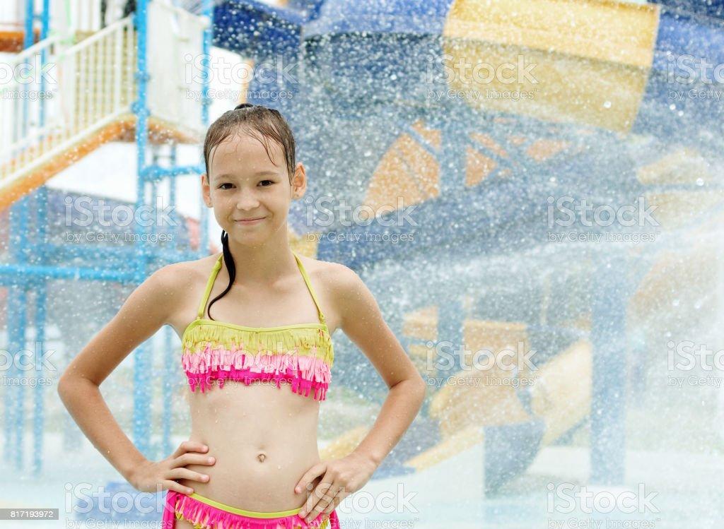 Smiling Preteen Girl Standing Under Water Drops In Water