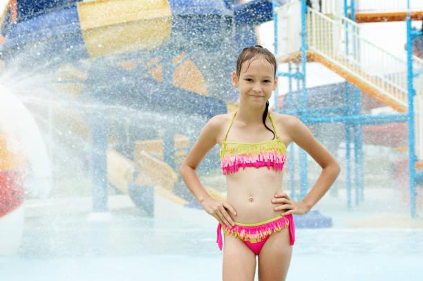 Smiling preteen girl standing under water drops stock photo