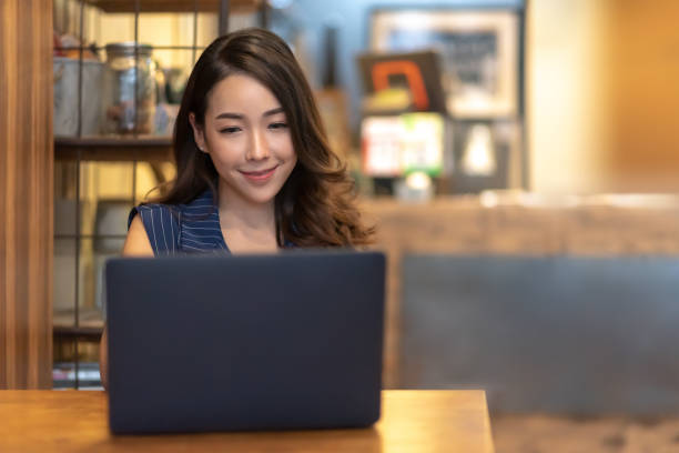 Smiling Pretty Asian woman making online reservation with laptop computer at Beautiful interior cafe. Young Charming Businesswoman relaxing and enjoying during doing video call meeting via internet, communication technology with people at restaurant. stock photo