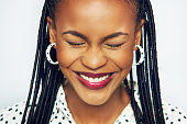 Beautiful face of pretty African-American woman with eyes closed making a wish and feeling cheerful.