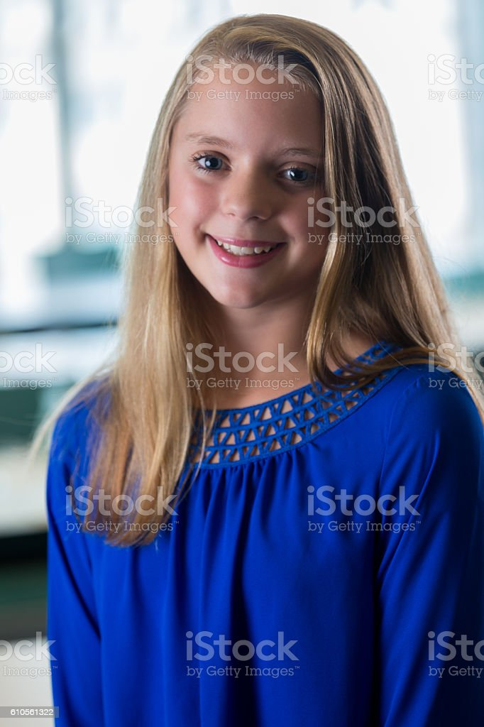 Young Pre Teen Girl Female Woman Torso Vertical Format: Smiling Pretty Blonde Preteen Girl Standing In A Classroom