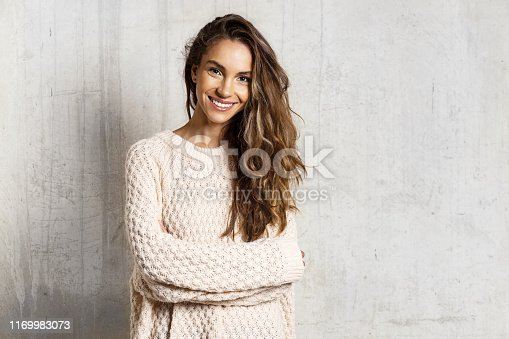 Portrait of young long-haired brunette woman standing on concrete background. Copy space in right side. Beauty and winter season concept