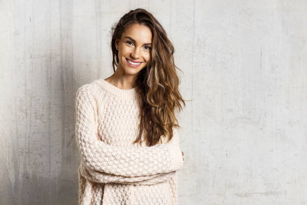 Smiling pretty girl in knitted sweater in studio stock photo