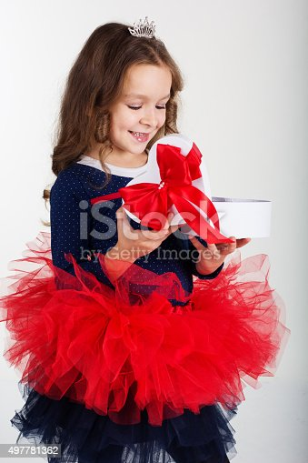 1061876006istockphoto Smiling pretty girl is holding gift box with red ribbon 497781362