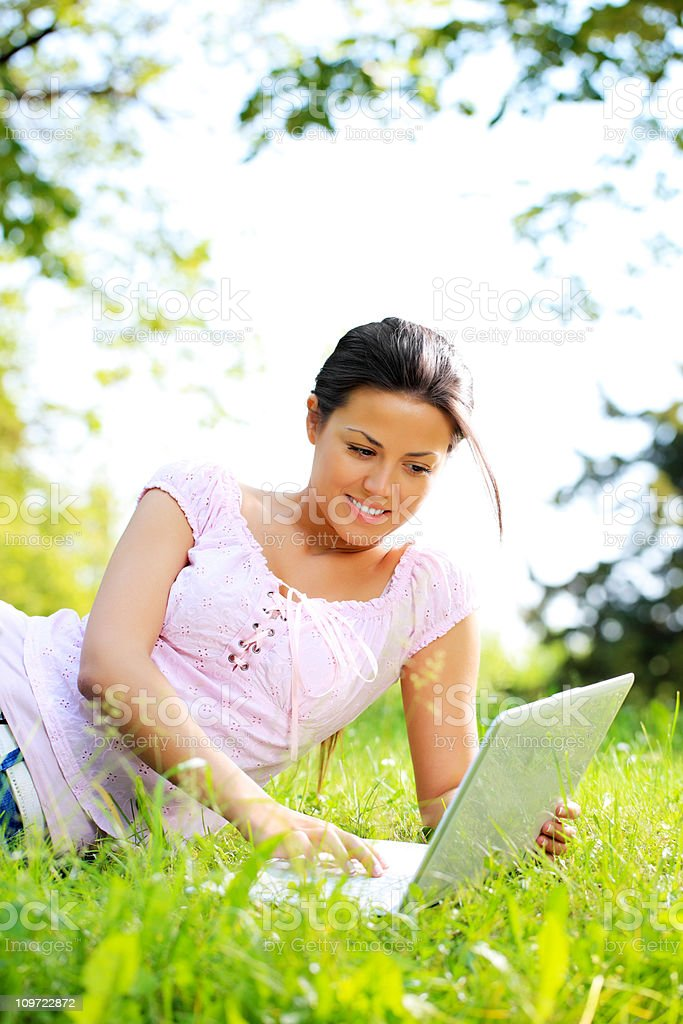Smiling pretty girl using laptop computer outdoor. royalty-free stock photo