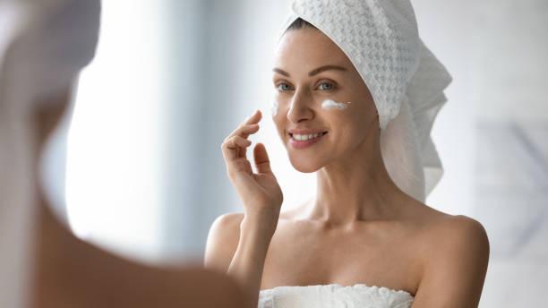 glimlachend mooie dame zet hydraterende gezichtscrème kijken in spiegel - creme huid stockfoto's en -beelden