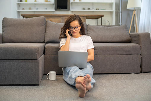 Smiling pretty lady talking on smartphone in living room