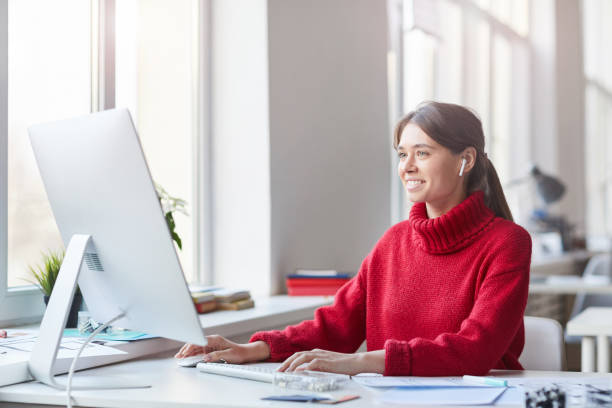 Smiling pretty skilled young woman in red knitted sweater and wireless earbuds sitting at table in office and working with modern computer stock photo