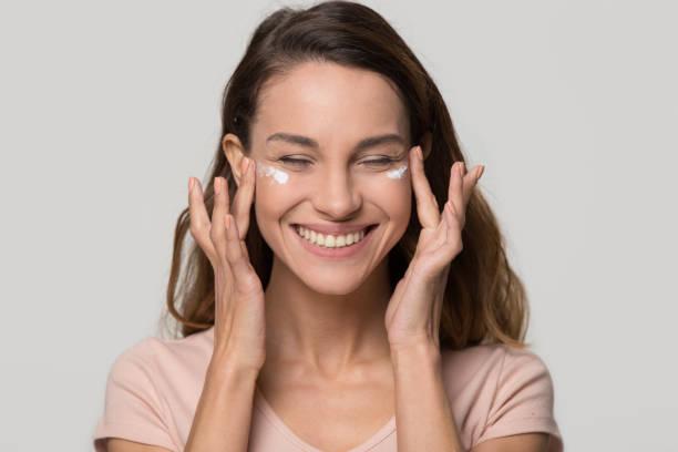 lachende vrij tiener meisje toepassing hydraterende cosmetische crème op gezicht - huidverzorging stockfoto's en -beelden