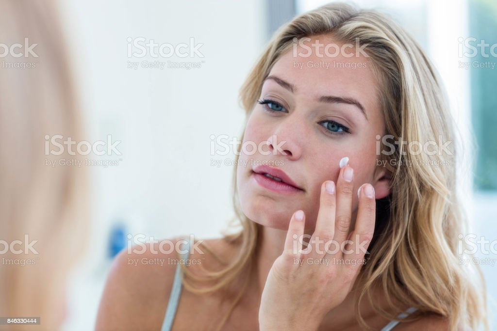 Smiling pretty woman applying cream on her face stock photo