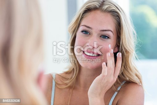 istock Smiling pretty woman applying cream on her face 846330506