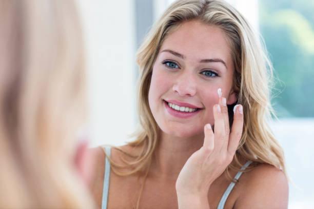 mulher bonita, aplicar o creme no rosto a sorrir - filtro solar - fotografias e filmes do acervo