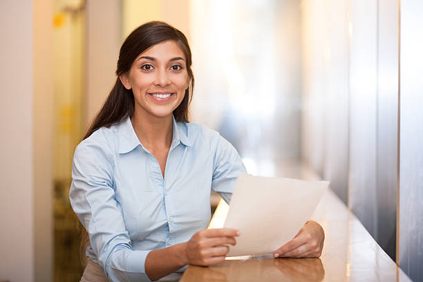 Smiling Pretty Woman Holding Document in Cafe Closeup portrait of smiling at camera pretty adult Indian woman sitting at table in cafe and holding document indigenous peoples of the americas stock pictures, royalty-free photos & images