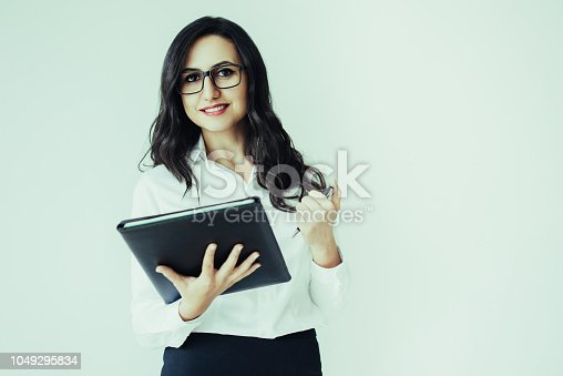 istock Smiling Pretty Woman Holding Folder and Pen 1049295834