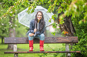 istock Smiling pretty woman holding umbrella on her shoulder sits on a bench back-rest in the park in the rain. 1240302368
