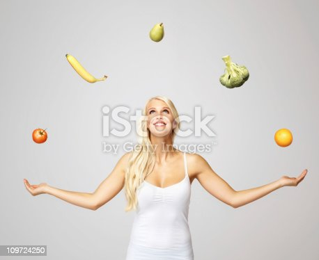 istock Smiling pretty woman juggling fruits and vegetables 109724250