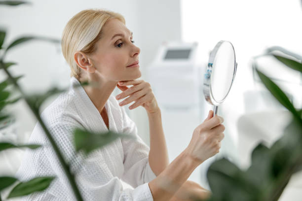 Smiling pretty woman using mirror in spa center stock photo