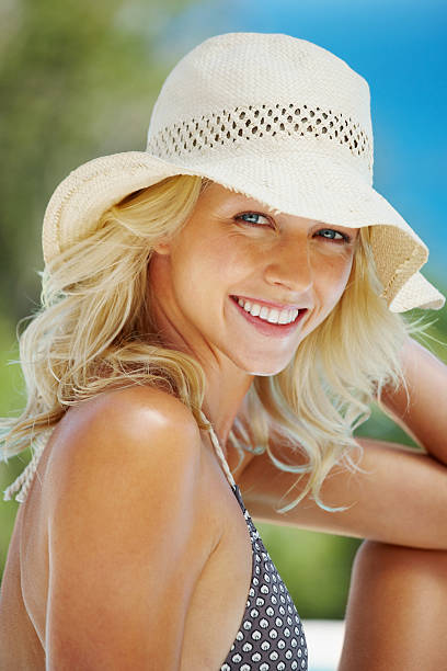 Smiling pretty woman wearing a bech hat stock photo