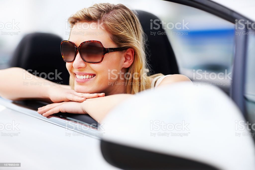 Smiling, pretty woman wearing sunglasses and resting at car door royalty-free stock photo