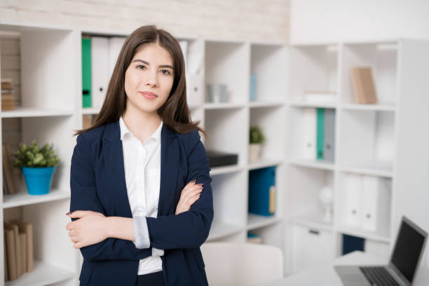 Smiling pretty young intern in office stock photo