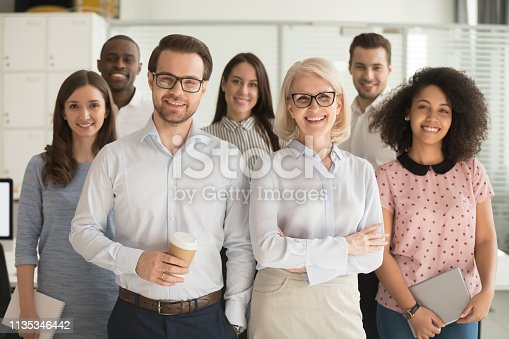 istock Smiling professional business leaders and employees group team portrait 1135346442
