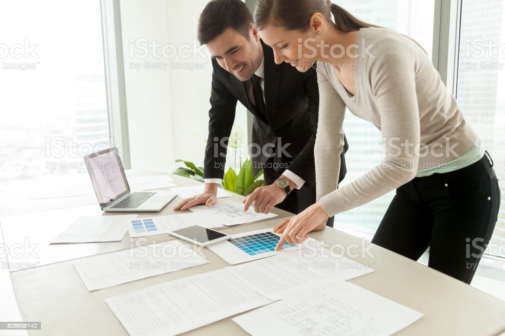 Smiling professional designers working on project, residential interior design services stock photo