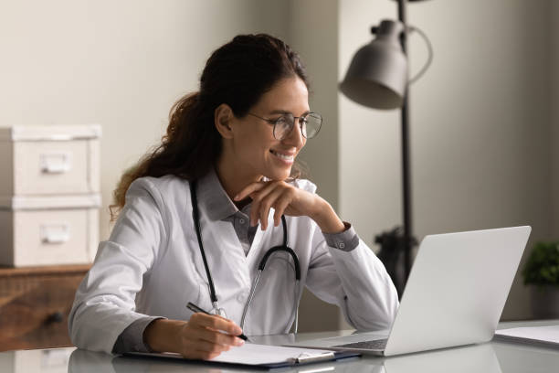 Smiling professional female doctor taking notes, looking at laptop screen stock photo