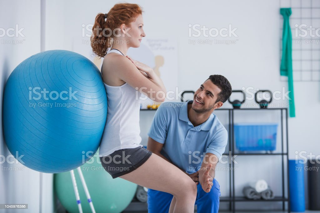 Smiling professional personal trainer helping sportswoman exercising...