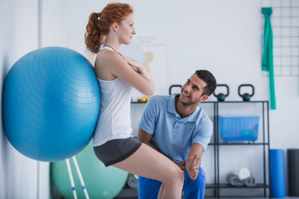 Smiling professional personal trainer helping sportswoman exercising with ball stock photo